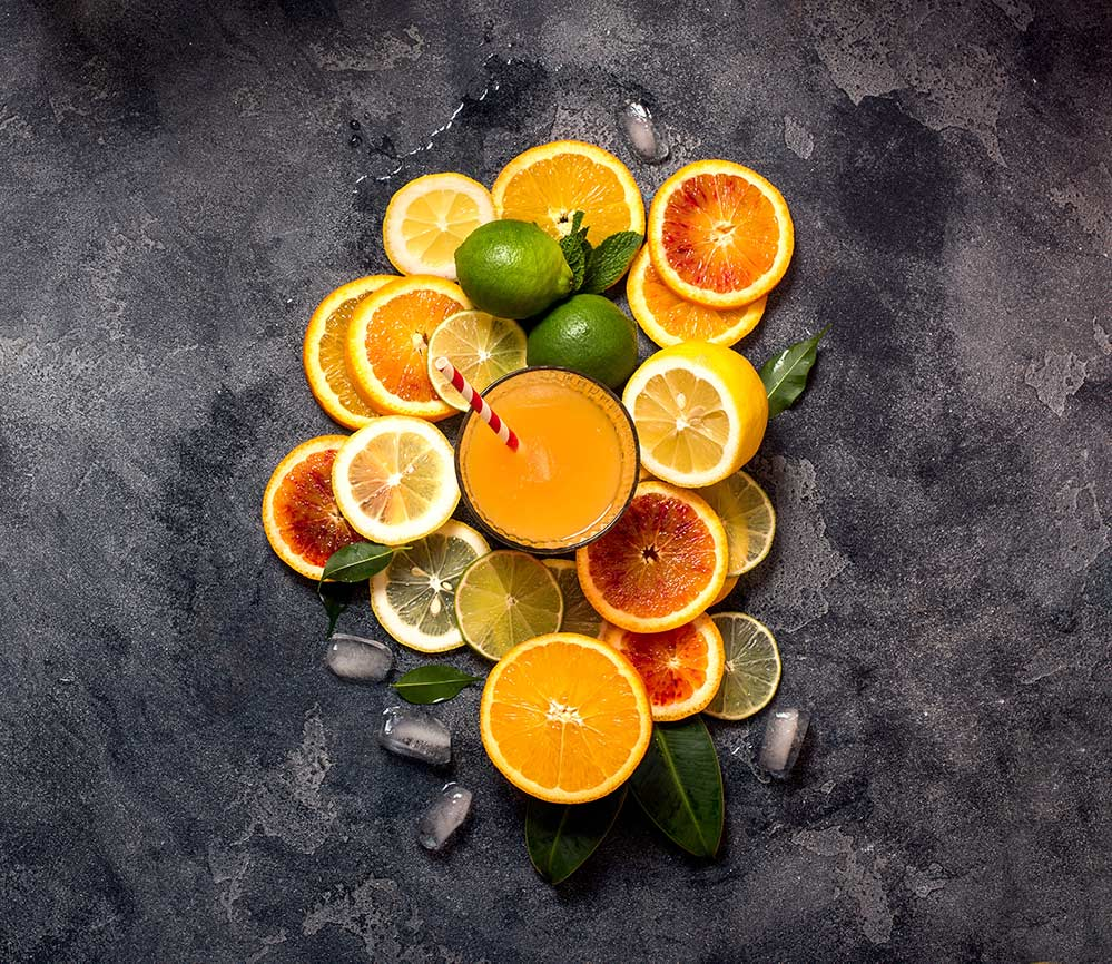 glass of citrus juice surrounded by sliced citrus fruits on a stone background with scattered ice cubes