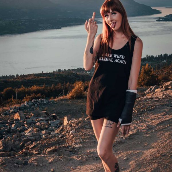 girl wearing black make weed illegal again tank top and giving the finger and sticking her tongue out