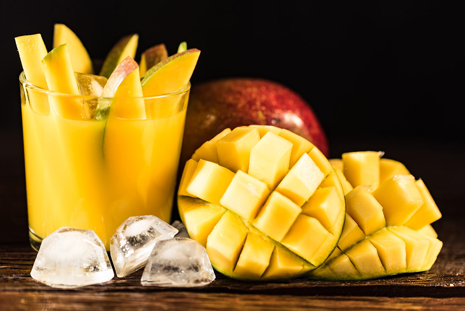 Mangos chopped, sliced and sitting in a glass of mango juice on a wooden cutting board with ice cubes in front of glass