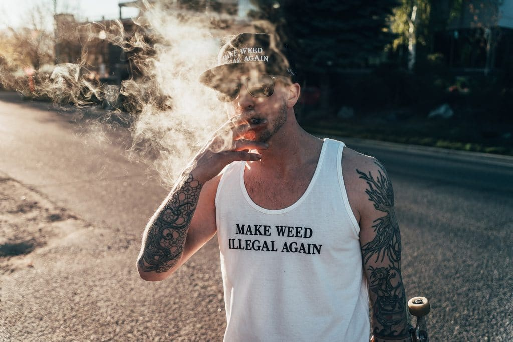 Man smoking joint on street wearing sessions apparel