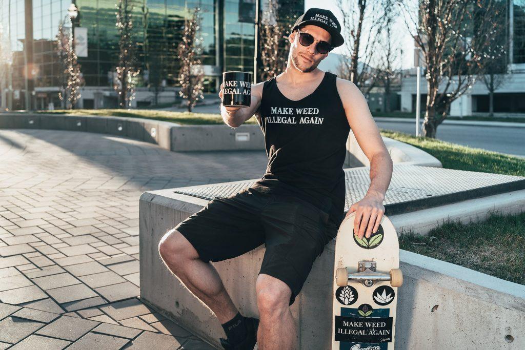 Man sitting with skateboard and coffee mug