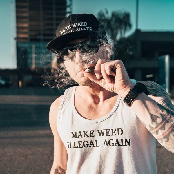 Man puffing joint on street wearing sessions apparel