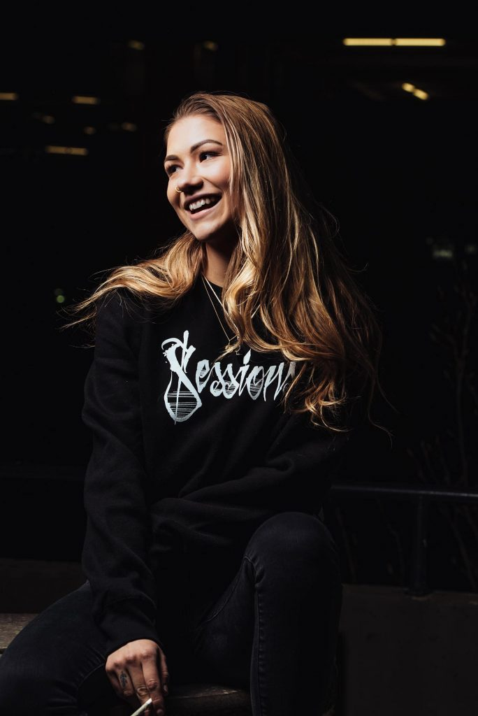 Woman laughing and holding joint in black sessions branded sweater