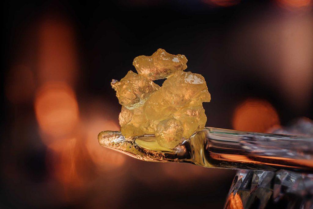 macro close up of yellow and orange thc diamonds sitting atop a glass stick